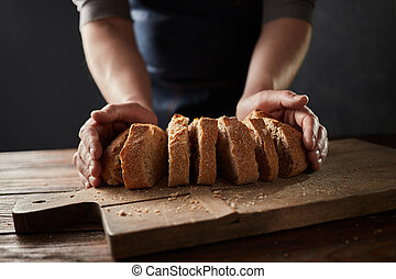 Fresh slice home bread in male's hands on wooden table
