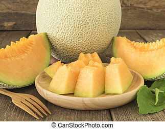 melon - Fresh sliced melon pieces in wood plate.