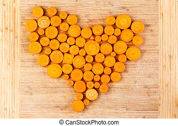 Fresh sliced orange carrots arranged in a heart