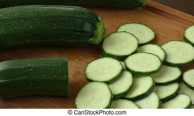 Fresh sliced zucchini on cutting board, on wooden background