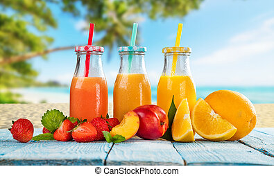 Fresh smoothie drinks placed on wooden planks, blur tropical beach on background. Summer drinks and beach vacation background