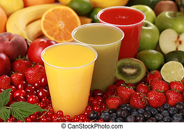 Cups filled with different kinds of smoothies surrounded by fresh fruits