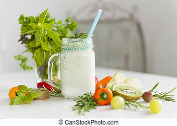 Fresh smoothies on a table with bright vegetables and a bunch of green herbs close up
