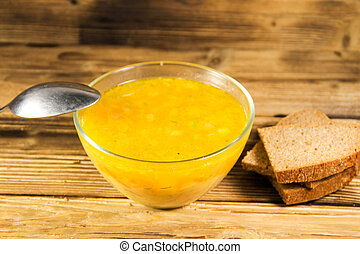Fresh soup in glass bowl on wooden table