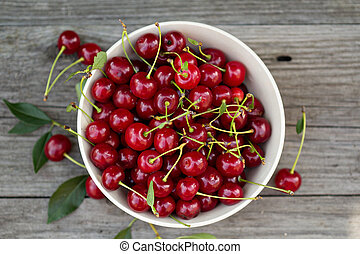 Fresh sour cherry in a bowl on a wooden table