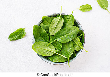 Fresh spinach leaves and a bowl, top view.