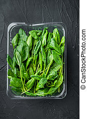 Fresh spinach leaves, on black background, in plastic pack, top view flat lay