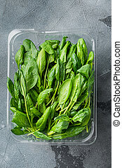 Fresh spinach leaves, on gray background, in plastic pack, top view flat lay