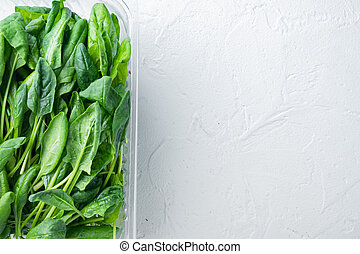 Fresh spinach leaves, on white background, in plastic pack, top view flat lay , with space for text copyspace