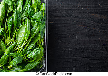 Fresh spinach , on black wooden table background, in plastic pack, top view flat lay , with space for text copyspace