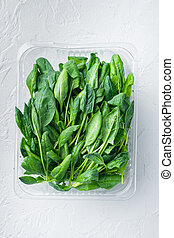 Fresh spinach , on white background, in plastic pack, top view flat lay