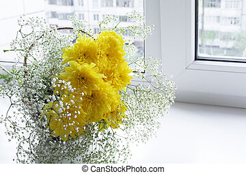 Fresh spring flowers in a vase on a window sill