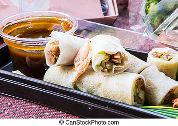 Fresh spring rolls, vegetables wrapped in dough, topped with crab meat and chili, eaten with sauce