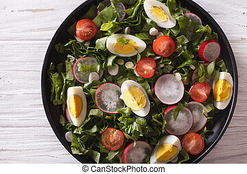 Fresh spring salad on a table close-up. horizontal top view