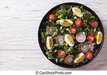 Fresh spring salad with eggs on a table. horizontal top view