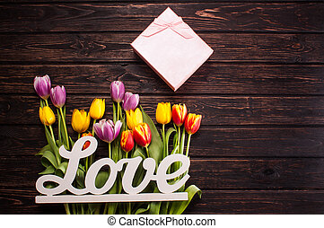 Fresh spring tulips flowers and word love on dark wooden background.