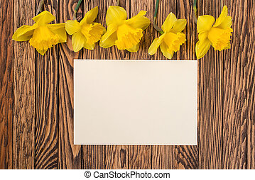 Fresh  spring yellow  daffodils  flowers and empty tag on brown painted wooden planks. Selective focus. Place for text.