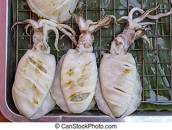 Fresh squid grilled on the steel mesh.