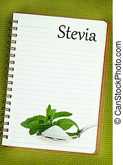 Fresh Stevia Rebaudiana and sugar on blank notebook page