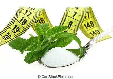 Fresh Stevia Rebaudiana, sugar in a spoon and measuring tape
