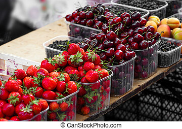 fresh strawberries and cherries at the grocery store