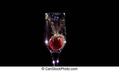 Fresh strawberries falling in glass with champagne wine. Slow motion