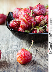 fresh strawberries in a black bowl on the table