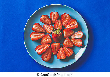 Fresh strawberries in a blue plate on a dark blue background