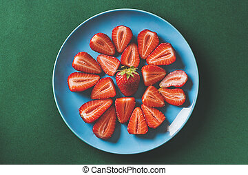 Fresh strawberries in a blue plate on a dark green background