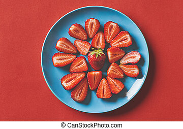Fresh strawberries in a blue plate on a red background