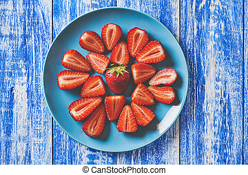 Fresh strawberries in a blue plate on a wooden white and blue background
