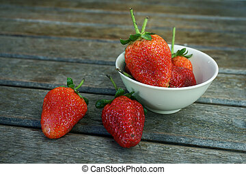 Fresh strawberries in bowl on wooden table