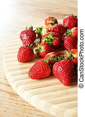 fresh strawberries on a chopping board
