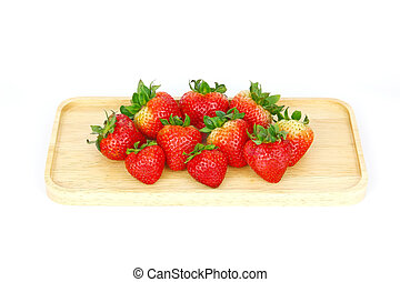 Fresh strawberries on the wooden plate