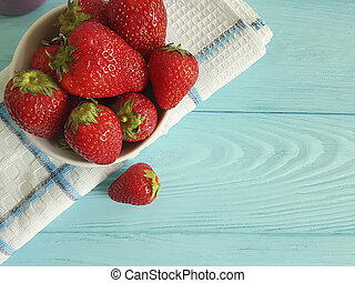 fresh strawberry dish towel on a blue wooden background