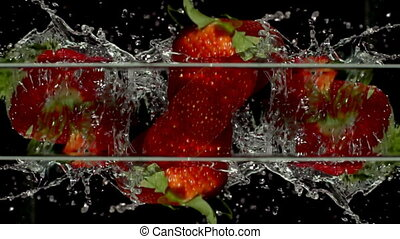 fresh strawberry fruit dropped into water shot in super slow motion with the sony FS700 high speed camera