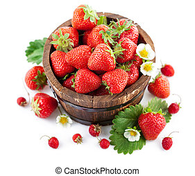 Fresh strawberry in wooden bucket with green leaf and flower...