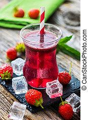 Fresh strawberry juice on wooden background