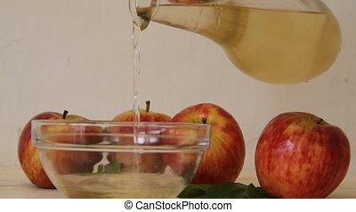 stream of apple cider vinegar falling from the bottle -...