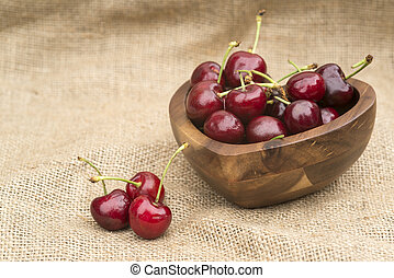 Macro of fresh Summer cherries in wooden bowl