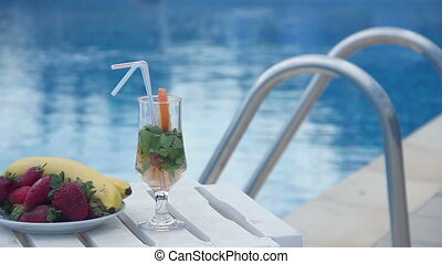 Fresh summer cocktail, fruit near swimming pool, all...