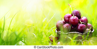 Fresh summer fruit background; healthy summer food; fresh cherry fruit on a green background