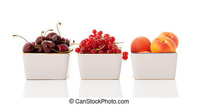 White bowls with fresh soft summer fruit