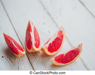 Fresh summer grapefruit slices composition on white wooden planks background