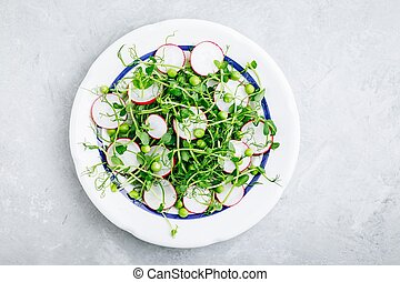 Fresh summer green pea shoots salad with radishes. Top view