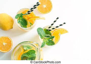 Fresh summer lemonade with citrus and mint on yellow background. Top view. Copy space.