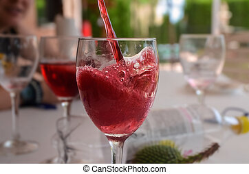 Fresh summer red wine falling into the glass