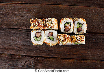 Fresh sushi roles on a wooden plate with hands of the chef in the background