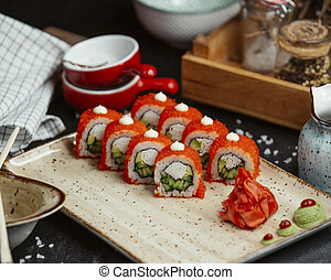 fresh sushi with red caviar on wooden board