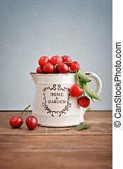Fresh sweet cherries in bowl on wooden table